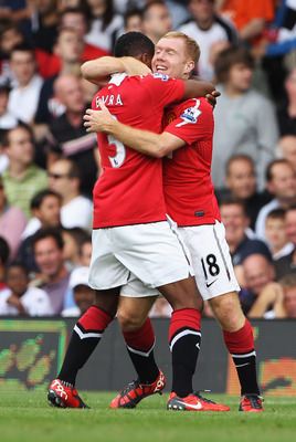 LONDON, ENGLAND - AUGUST 22:  Paul Scholes of Manchester United celebrates with Patrice Evra as he scores their first goal during the Barclays Premier League match between Fulham and Manchester United at Craven Cottage on August 22, 2010 in London, Englan