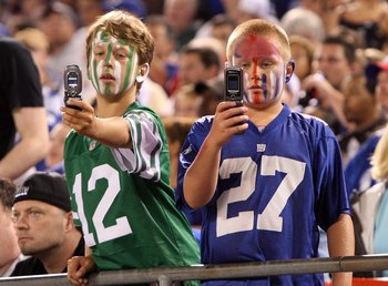EAST RUTHERFORD, NJ - AUGUST 29:  Young fans of the New York Giants and the New York Jets take photographs during a pre season game on August 29, 2009 at Giants Stadium in East Rutherford, New Jersey.  (Photo by Jim McIsaac/Getty Images)