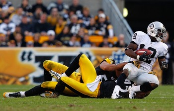 PITTSBURGH, PA - NOVEMBER 21:  Ryan Clark #25 and James Farrior #51 of the Pittsburgh Steelers tackle Jacoby Ford #12 of the Oakland Raiders during the game on November 21, 2010 at Heinz Field in Pittsburgh, Pennsylvania.  (Photo by Jared Wickerham/Getty