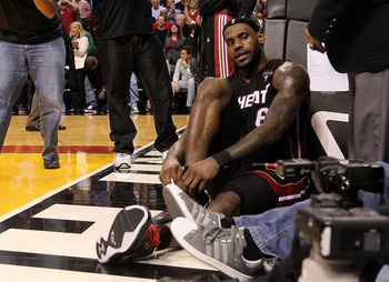 MIAMI, FL - MARCH 10:  LeBron James #6 of the Miami Heat ties his shoe after falling on a camerman during a game against  the Los Angeles Lakers at American Airlines Arena on March 10, 2011 in Miami, Florida. NOTE TO USER: User expressly acknowledges and