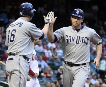 PHOENIX, AZ - MAY 16:  Chase Headley #7 of the San Diego Padres high fives teammate Kyle Phillips #16 after scoring a first inning run against the Arizona Diamondbacks during the Major League Baseball game at Chase Field on May 16, 2011 in Phoenix, Arizon