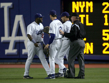 LOS ANGELES - SEPTEMBER 28:  Right fielder Milton Bradley #21 of the Los Angeles Dodgers is restrained by Steve Finley #12, Alex Cora #3 and umpire Jim Joyce after an incident with a fan after Bradley's error against the Colorado Rockies allowed two runs