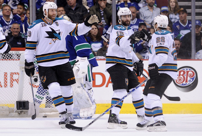 VANCOUVER, CANADA - MAY 15: Joe Thornton #19 and Dan Boyle #22 of the San Jose Sharks congratulate teammate Patrick Marleau #12 after Marleau's goal against the Vancouver Canucks in the second period in Game One of the Western Conference Finals during the