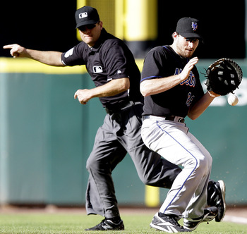 HOUSTON - MAY 14:  First baseman Daniel Murphy #28 of the New York Mets fields a ball as first base umpire Chad Fairchild signals fair at Minute Maid Park on May 14, 2011 in Houston, Texas.  (Photo by Bob Levey/Getty Images)