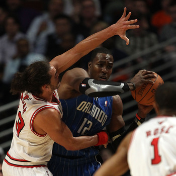 CHICAGO, IL - DECEMBER 01: Dwight Howard #12 of the Orlando Magic looks to pass under pressure from Joakim Noah #13 of the Chicago Bulls at the United Center on December 1, 2010 in Chicago, Illinois. The Magic defeated the Bulls 107-78. NOTE TO USER: User