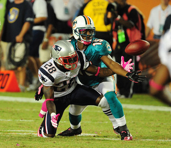MIAMI - OCTOBER 4: Davone Bess #15 of the Miami Dolphins battles for a pass against Darius Butler #28 of the New England Patriots at Sun Life Field on October 4, 2010 in Miami, Florida. (Photo by Scott Cunningham/Getty Images)