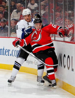 NEWARK, NJ - JANUARY 09: Steve Downie #9 of the Tampa Bay Lightning takes down Andy Greene #6 of the New Jersey Devils in the third period of an NHL hockey game at the Prudential Center on January 9, 2011 in Newark, New Jersey. (Photo by Paul Bereswill/Ge