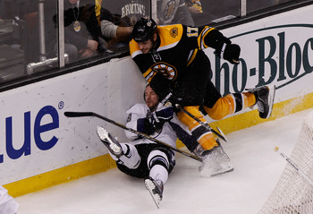 BOSTON, MA - MAY 14:  Adam Hall #18 of the Tampa Bay Lightning is checked by Milan Lucic #17 of the Boston Bruins in the third period of Game One of the Eastern Conference Finals during the 2011 NHL Stanley Cup Playoffs at TD Garden on May 14, 2011 in Bos
