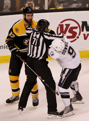 BOSTON, MA - MAY 17:  linesman Brad Kovachik #71 breaks up a fight between Zdeno Chara #33 of the Boston Bruins and Steve Downie #9 of the Tampa Bay Lightning in Game Two of the Eastern Conference Finals during the 2011 NHL Stanley Cup Playoffs at TD Gard