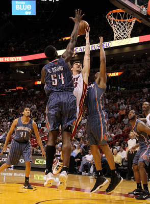 MIAMI, FL - APRIL 08:  Mike Miller #13 of the Miami Heat drives against Kwame Brown #54 and Dominic McGuire #5 of the Charlotte Bobcats during a game at American Airlines Arena on April 8, 2011 in Miami, Florida. NOTE TO USER: User expressly acknowledges