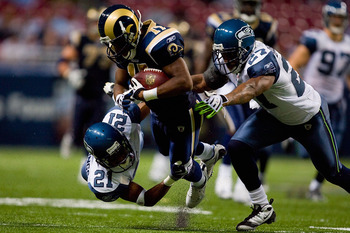 ST. LOUIS - NOVEMBER 29:  Donnie Avery #17 of the St. Louis Rams is tackled by Kelly Jennings #21 and Jordan Babineaux #27 both of the Seattle Seahawks at the Edward Jones Dome on November 29, 2009 in St. Louis, Missouri.  (Photo by Dilip Vishwanat/Getty