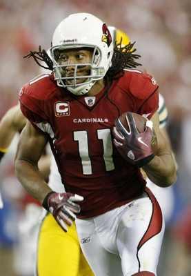 GLENDALE, AZ - JANUARY 10:  Wide receiver Larry Fitzgerald #11 of the Arizona Cardinals runs for a touchdown in the third quarter of the 2010 NFC wild-card playoff game against the Green Bay Packers at University of Phoenix Stadium on January 10, 2010 in