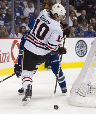 VANCOUVER, CANADA - APRIL 26: Patrick Sharp #10 of the Chicago Blackhawks makes a pass while falling as Kevin Bieksa #3 of the Vancouver Canucks looks on during the second period in Game Seven of the Western Conference Quarterfinals during the 2011 NHL St