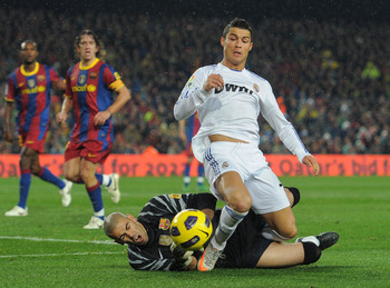 BARCELONA, SPAIN - NOVEMBER 29:  Cristiano Ronaldo (R) of Real Madrid is fouled in the penalty aeria by goalkeeper Victor Valdes of Barcelona during the la liga match between Barcelona and Real Madrid at the Camp Nou stadium on November 29, 2010 in Barcel