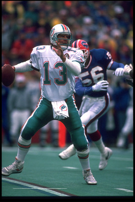 23 DEC 1990:  DAN MARINO #13, QUARTERBACK FOR THE MIAMI DOLPHINS, SCRAMBLES AWAY FROM BUFFALO BILLS LINEBACKER DARRYL TALLEY #56 DURING THE BILLS'' 24-14 WIN AT RICH STADIUM IN ORCHARD PARK, NEW YORK.  MANDATORY CREDIT:  RICK STEWART/ALLSPORT