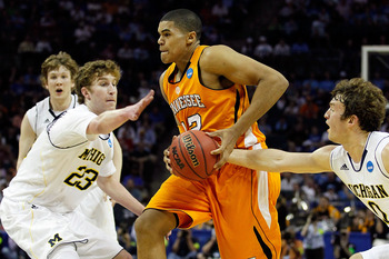 CHARLOTTE, NC - MARCH 18:  Tobias Harris #12 of the Tennessee Volunteers drives through Evan Smotrycz #23 and Zack Novak #0 of the Michigan Wolverines in the first half during the second round of the 2011 NCAA men's basketball tournament at Time Warner Ca