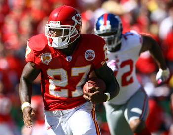 KANSAS CITY, MO - OCTOBER 04:  Running back Larry Johnson #27 of the Kansas City Chiefs carries the ball as Osi Umenyiora #72 of the New York Giants gives chase during the game on October 4, 2009 at Arrowhead Stadium in Kansas City, Missouri.  (Photo by J
