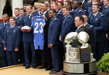 WASHINGTON - APRIL 18:  U.S. President Barack Obama (C) poses for a group picture with members of the Air Force Academy football team, including defensive back Reggie Rembert on his left, fullback Jared Tew on his right, and head coach Troy Calhoun, right