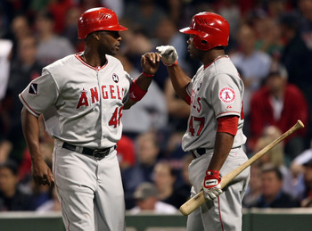 BOSTON - SEPTEMBER 15:  Torii Hunter #468 of the Los Angeles Angels of Anaheim is congratulated by teammate Howie Kendrick #47 after Hunter scored a run in the ninth inning against the Boston Red Sox on September 15, 2009 at Fenway Park in Boston, Massach