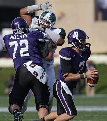 EVANSTON, IL - OCTOBER 23: Dan Persa #7 of the Northwestern Wildcats looks for a receiver as teammate Brain Mulroe #72 blocks Jerel Worthy #99 of the Michigan State Spartans at Ryan Field on October 23, 2010 in Evanston, Illinois. Michigan State defeated