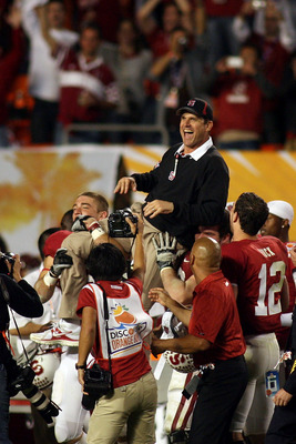 MIAMI, FL - JANUARY 03:  Head coach Jim Harbaugh of the Stanford Cardinal is lifted up by his players as they celebrate their 40-12 win against the Virginia Tech Hokies during the 2011 Discover Orange Bowl at Sun Life Stadium on January 3, 2011 in Miami,