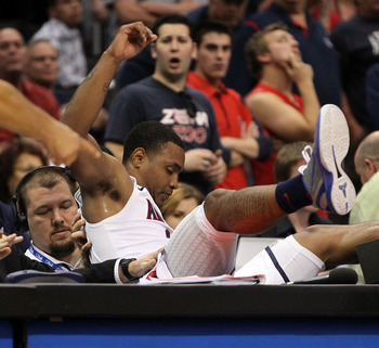 LOS ANGELES, CA - MARCH 12:  Lamont Jones #12 of the Arizona Wildcats falls into the scorer's table in overtime while taking on the Washington Huskies the championship game of the 2011 Pacific Life Pac-10 Men's Basketball Tournament at Staples Center on M
