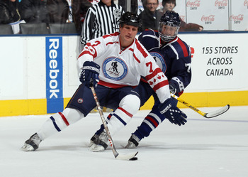 TORONTO, ON - NOVEMBER 07: Paul Coffey #77 of the Canada Legends moves the puck around Sue Merz of the USA Legends at the Legends Classic Hockey Game at the Air Canada Centre on November 7, 2010 in Toronto, Canada.  (Photo by Bruce Bennett/Getty Images)