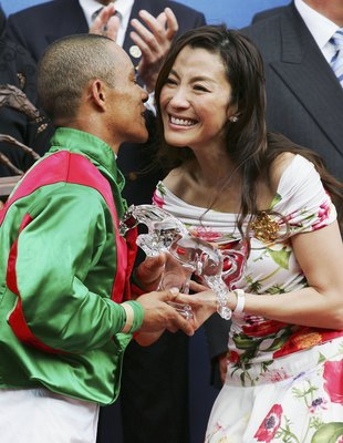 HONG KONG, CHINA - APRIL 23:  Irridescence jockey Weichong Marwing receives the trophy from Malaysian actress Michelle Yeoh after winning the Audemars Piguet Queen Elizabeth II Cup at Shatin Racecourse April 23, 2006 in Hong Kong, China.  (Photo by MN Cha