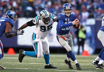 EAST RUTHERFORD, NJ - DECEMBER 27:  Eli Manning #10 of the New York Giants is chased down Charles Johnson #95 of the Carolina Panthers at Giants Stadium on December 27, 2009 in East Rutherford, New Jersey.  (Photo by Nick Laham/Getty Images)
