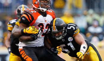 PITTSBURGH - DECEMBER 12:  Reggie Kelly #82 of the Cincinnati Bengals is hit by James Farrior #51 of the Pittsburgh Steelers after catching a pass during the game on December 12, 2010 at Heinz Field in Pittsburgh, Pennsylvania.  (Photo by Jared Wickerham/