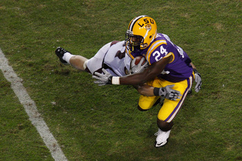 BATON ROUGE, LA - NOVEMBER 13:  Alfred Blue #24 of the Louisiana State University Tigers is tackled by Ty Kittle #87 of the University of Louisiana-Monroe Warhawks at Tiger Stadium on November 13, 2010 in Baton Rouge, Louisiana.   The Tigers defeated the