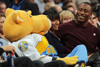 DENVER, CO - FEBRUARY 10:  Rocky (L), the mascot of the Denver Nuggets interacts with Brandon Marshall (R), wide receiver for the Miami Dolphins and his companion (C) as they sit courtside as the Nuggets face the Dallas Mavericks during NBA action at the