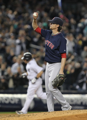 NEW YORK, NY - MAY 13: Clay Buchholz #11 of the Boston Red Sox reacts after giving up a home run to Russell Martin #55 of the New York Yankees who is rounding the bases during their game on May 13, 2011 at Yankee Stadium in the Bronx borough of New York C