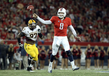 TUCSON, AZ - DECEMBER 02:  Quarterback Nick Foles #8 of the Arizona Wildcats throws a pass under pressure from Junior Onyeali #97 of the Arizona State Sun Devils during the college football game at Arizona Stadium on December 2, 2010 in Tucson, Arizona.