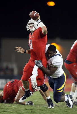 TUCSON, AZ - SEPTEMBER 25:  Quarterback Nick Foles #8 of the Arizona Wildcats is pressured into throwing an incomplete pass by Cameron Jordan #97 of the California Bears during the first quarter of the college football game at Arizona Stadium on September