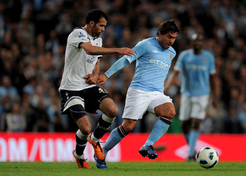 MANCHESTER, ENGLAND - MAY 10:  Carlos Tevez of Manchester City competes with Sandro of Tottenham Hotspur during the Barclays Premier League match between Manchester City and Tottenham Hotspur at the City of Manchester Stadium on May 10, 2011 in Manchester