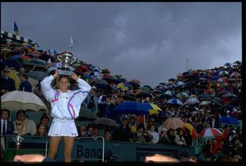 9 JUN 1990:  MONICA SELES OF YUGOSLAVIA SHIELDS HERSELF FROM THE RAIN WITH THE TROPHY AFTER DEFEATING STEFFI GRAF OF GERMANY IN THE FINAL OF THE 1990 FRENCH OPEN PLAYED AT ROLAND GARROS. SELES WON THE MATCH 7-6 (8-6) AND 6-4.