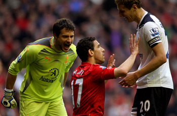 LIVERPOOL, ENGLAND - MAY 15:  Maxi Rodriguez of Liverpool incurs the wrath of Carlo Cudicini (L) and Michael Dawson (R) of Spurs during the Barclays Premier League match between Liverpool and Tottenham Hotspur at Anfield on May 15, 2011 in Liverpool, Engl