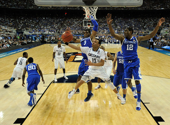 HOUSTON, TX - APRIL 02:  Shabazz Napier #13 of the Connecticut Huskies goes to the hoop against Terrence Jones #3 and Brandon Knight #12 of the Kentucky Wildcats during the National Semifinal game of the 2011 NCAA Division I Men's Basketball Championship