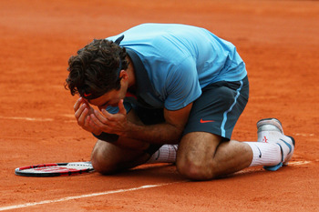 PARIS - JUNE 07:  Roger Federer of Switzerland falls to his knees as he celebrates victory during the Men's Singles Final match against Robin Soderling of Sweden on day fifteen of the French Open at Roland Garros on June 7, 2009 in Paris, France.  (Photo