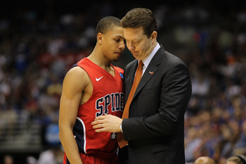 SAN ANTONIO, TX - MARCH 25:  Head coach Chris Mooney of the Richmond Spiders comforts Kevin Smith #12 after the southwest regional of the 2011 NCAA men's basketball tournament at the Alamodome on March 25, 2011 in San Antonio, Texas. Kansas defeated Richm