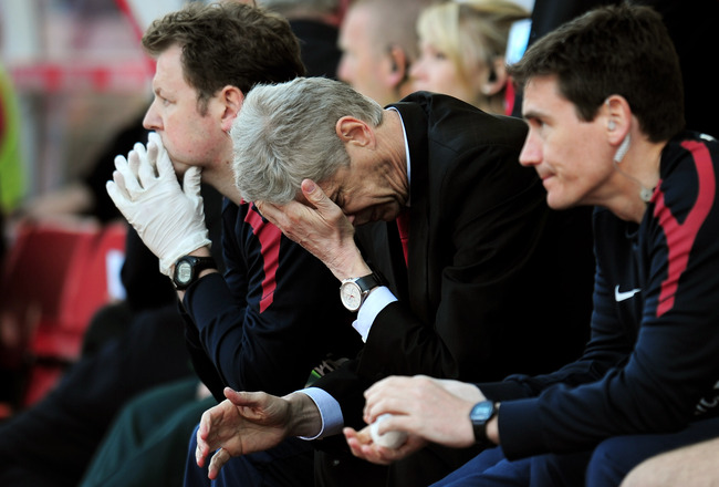 STOKE ON TRENT, ENGLAND - MAY 08:  A dejected Arsene Wenger the Arsenal manager holds his head in his hands as his team head towards a 3-1 defeat during the Barclays Premier League match between Stoke City and Arsenal at the Britannia Stadium on May 8, 20