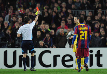 BARCELONA, SPAIN - MARCH 08:  Robin van Persie of Arsenal receives a red card from referee Massimo Busacca during the UEFA Champions League round of 16 second leg match between Barcelona and Arsenal at the Nou Camp Stadium on March 8, 2011 in Barcelona, S