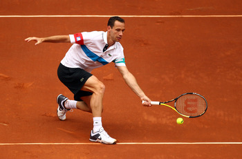 MADRID, SPAIN - MAY 06:  Michael Llodra of France plays a volley in his match against Rafael Nadal of Spain during day seven of the Mutua Madrilena Madrid Open Tennis on May 6, 2011 in Madrid, Spain.  (Photo by Julian Finney/Getty Images)