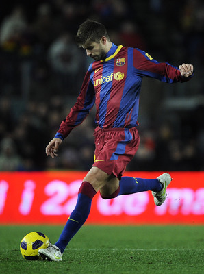 BARCELONA, SPAIN - JANUARY 22:  Gerard Pique of Barcelona passes the ball during the La Liga match between Barcelona and Racing Santander at Camp Nou on January 22, 2011 in Barcelona, Spain. Barcelona won 3-0.  (Photo by David Ramos/Getty Images)