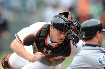 BALTIMORE - MAY 13:  Matt Wieters #32 of the Baltimore Orioles tags out Josh Wilson #16 of the Seattle Mariners for the final out at Camden Yards on May 13, 2010 in Baltimore, Maryland. The Orioles won the game 6-5.  (Photo by Greg Fiume/Getty Images)