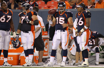 DENVER - AUGUST 29:  Quarterback Tim Tebow #15 of the Denver Broncos is prepared to enter the game as he stands on the bench with D'Anthony Batiste #67, Russ Hochstein #71 and LenDale White #26 against the Pittsburgh Steelers during preseason NFL action a