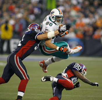 TORONTO, ON - DECEMBER 07: Anthony Fasano #80 of the Miami Dolphins is stopped by Paul Posluzny #51 and Donte Whitner #20 of the Buffalo Bills on December 7, 2008  at Rogers Centre in Toronto, Ontario, Canada. The Dolphins won 16-3. (Photo by Rick Stewart
