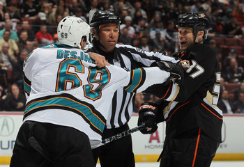 ANAHEIM, CA - APRIL 06:  Linesman Jay Sharrers seperates Andrew Desjardins #69 of the San Jose Sharks and Jarkko Ruutu #37 of the Anaheim Ducks in the second period at Honda Center on April 6, 2011 in Anaheim, California. The Ducks defeated the Sharks 6-2