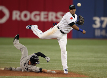 TORONTO, ON - APRIL 19:  Yunel Escobar #5 of the Toronto Blue Jays makes a play to get Nick Swisher #33 of the New York Yankees out at second base during their game at Rogers Centre on April 19, 2011 in Toronto, Canada.  (Photo by Scott Halleran/Getty Ima